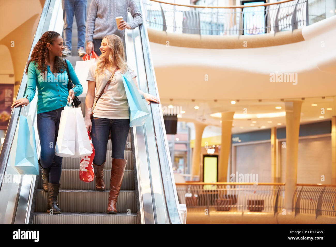 Two Female Friends On Escalator In Shopping Mall - Stock Image
