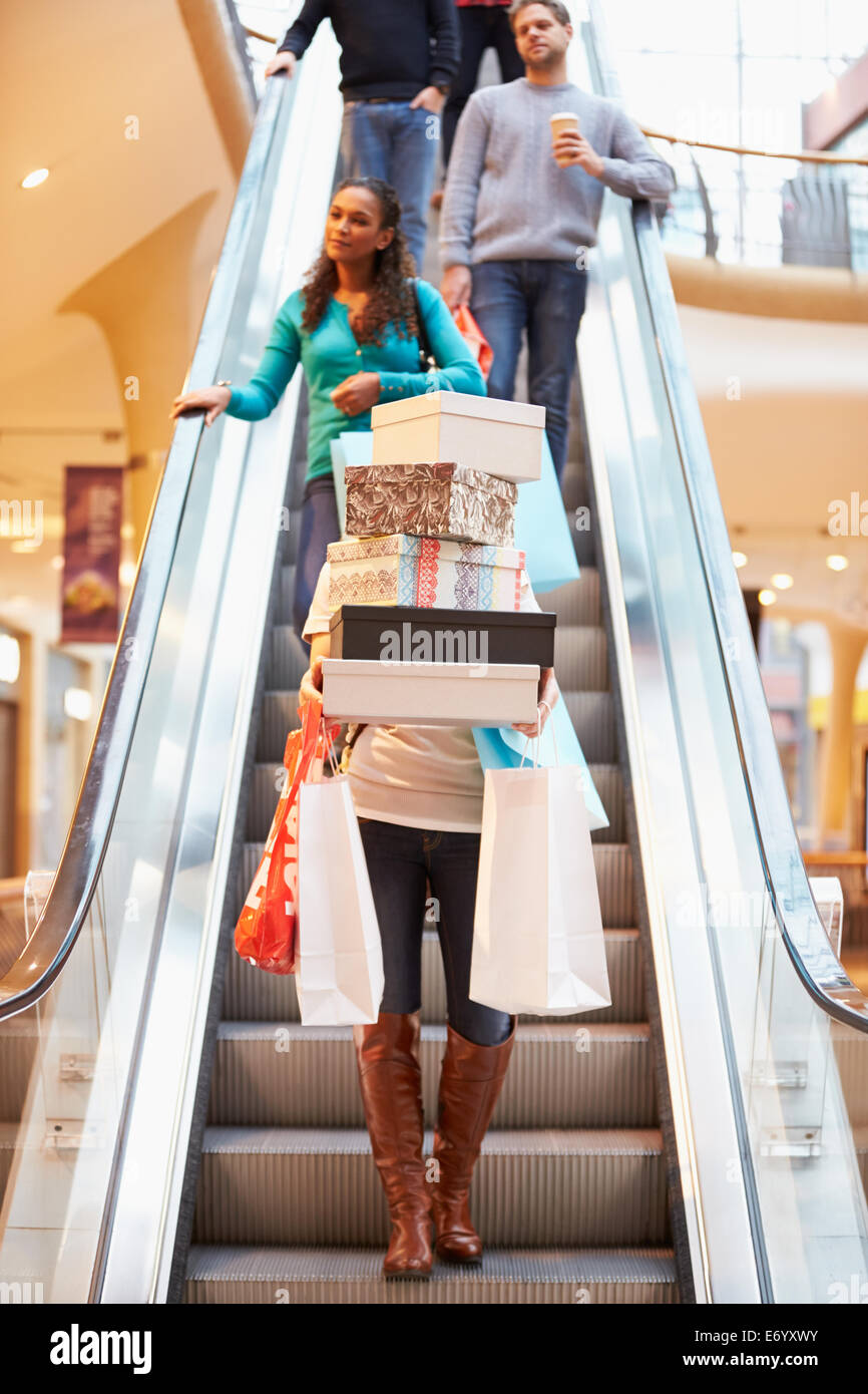 Woman Carrying Boxes And Bags In Shopping Mall - Stock Image