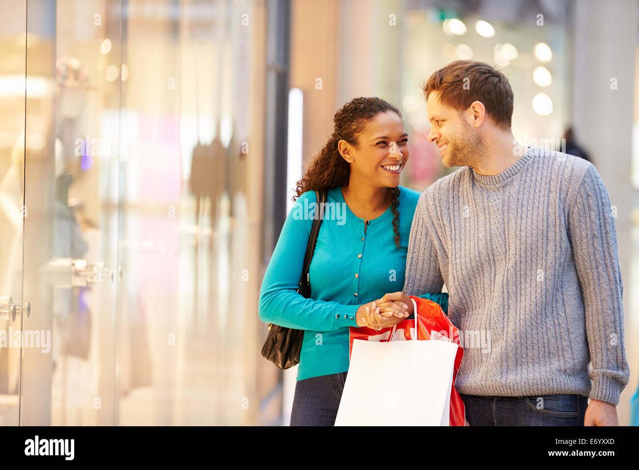 Happy Couple Carrying Bags In Shopping Mall - Stock Image