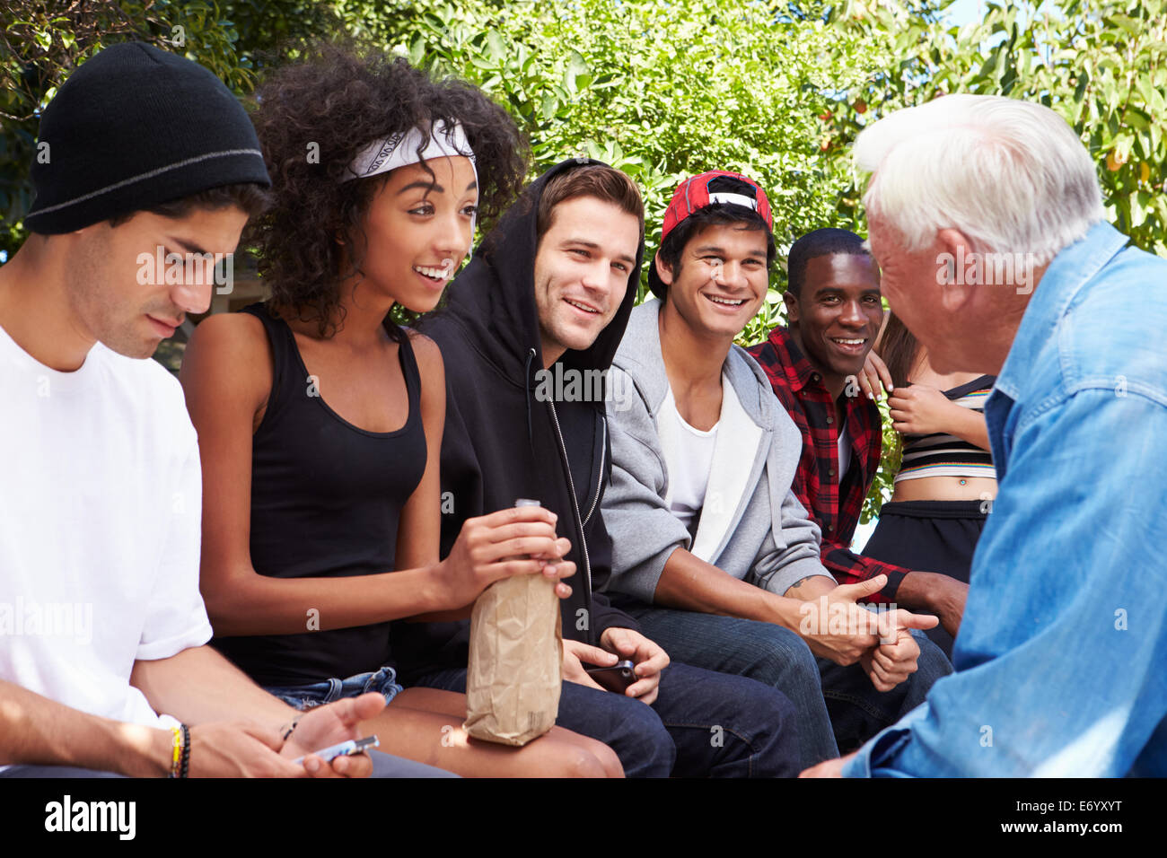 Senior Man Talking With Gang Of Young People - Stock Image