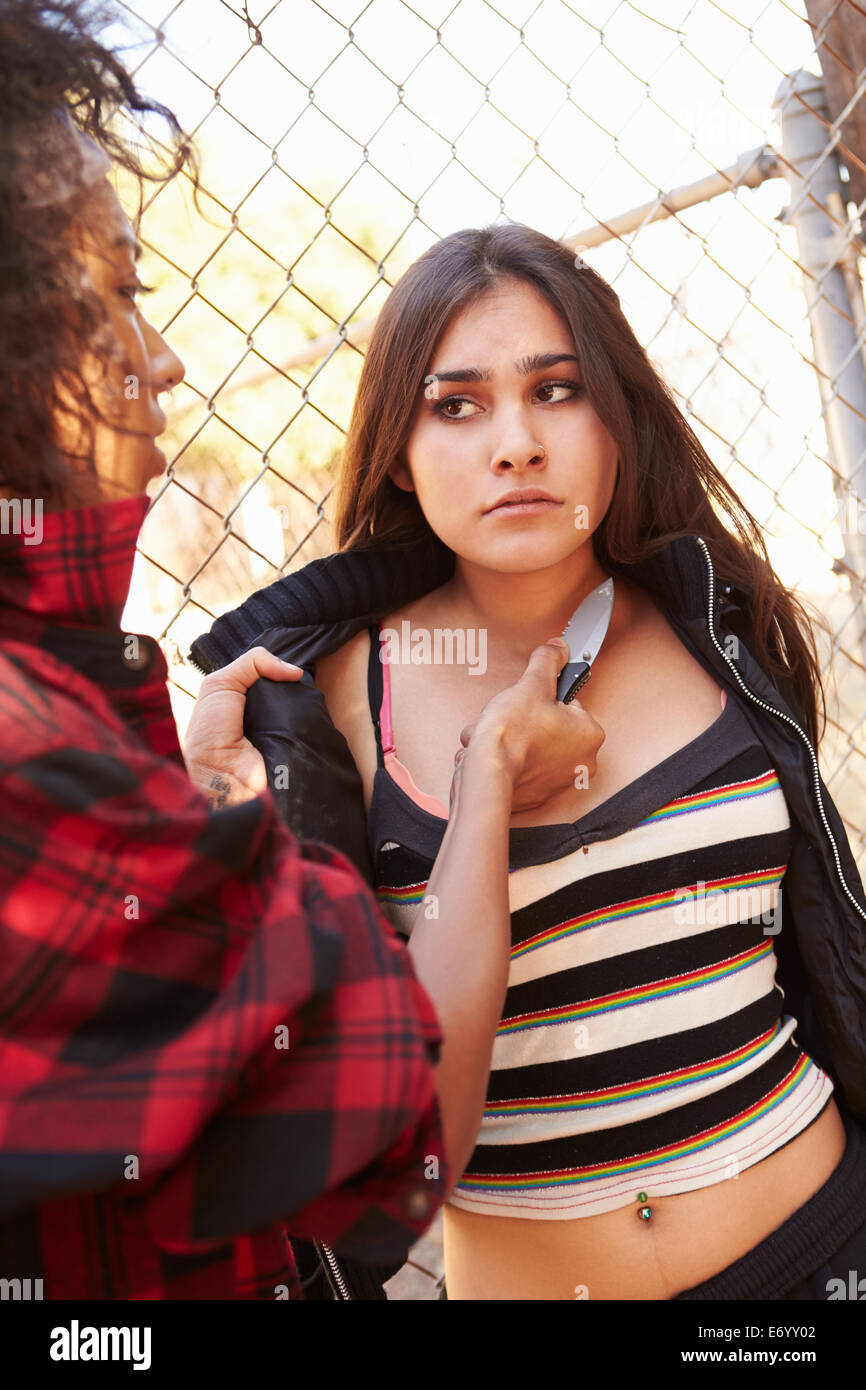 Girl Being Threatened With Knife By Female Gang Member - Stock Image