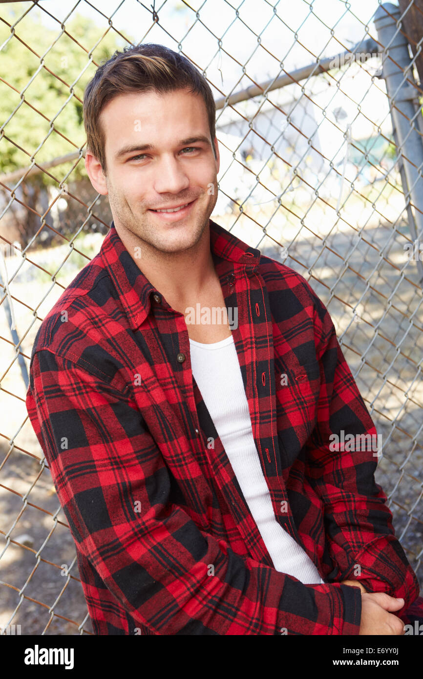 Portrait Of Young Man In Urban Setting Standing By Fence - Stock Image