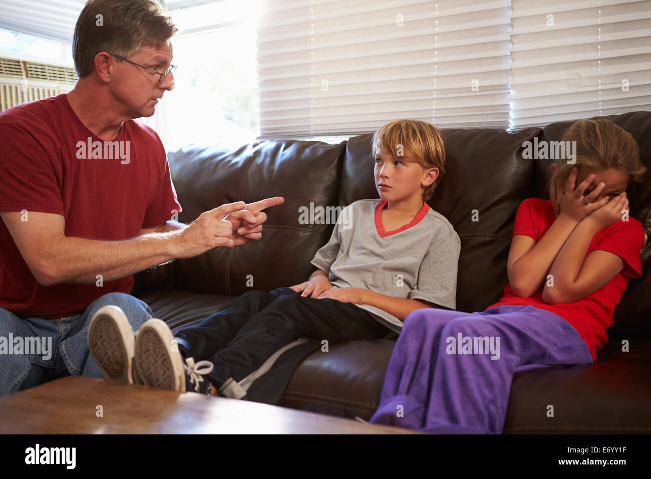 Father Being Physically Abusive Towards Children At Home - Stock Image