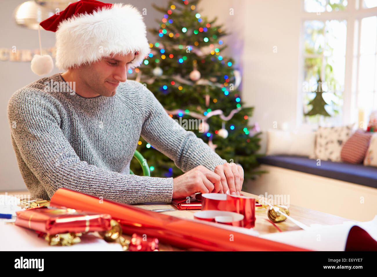 Man Wrapping Christmas Gifts At Home Stock Photo: 73143679 - Alamy