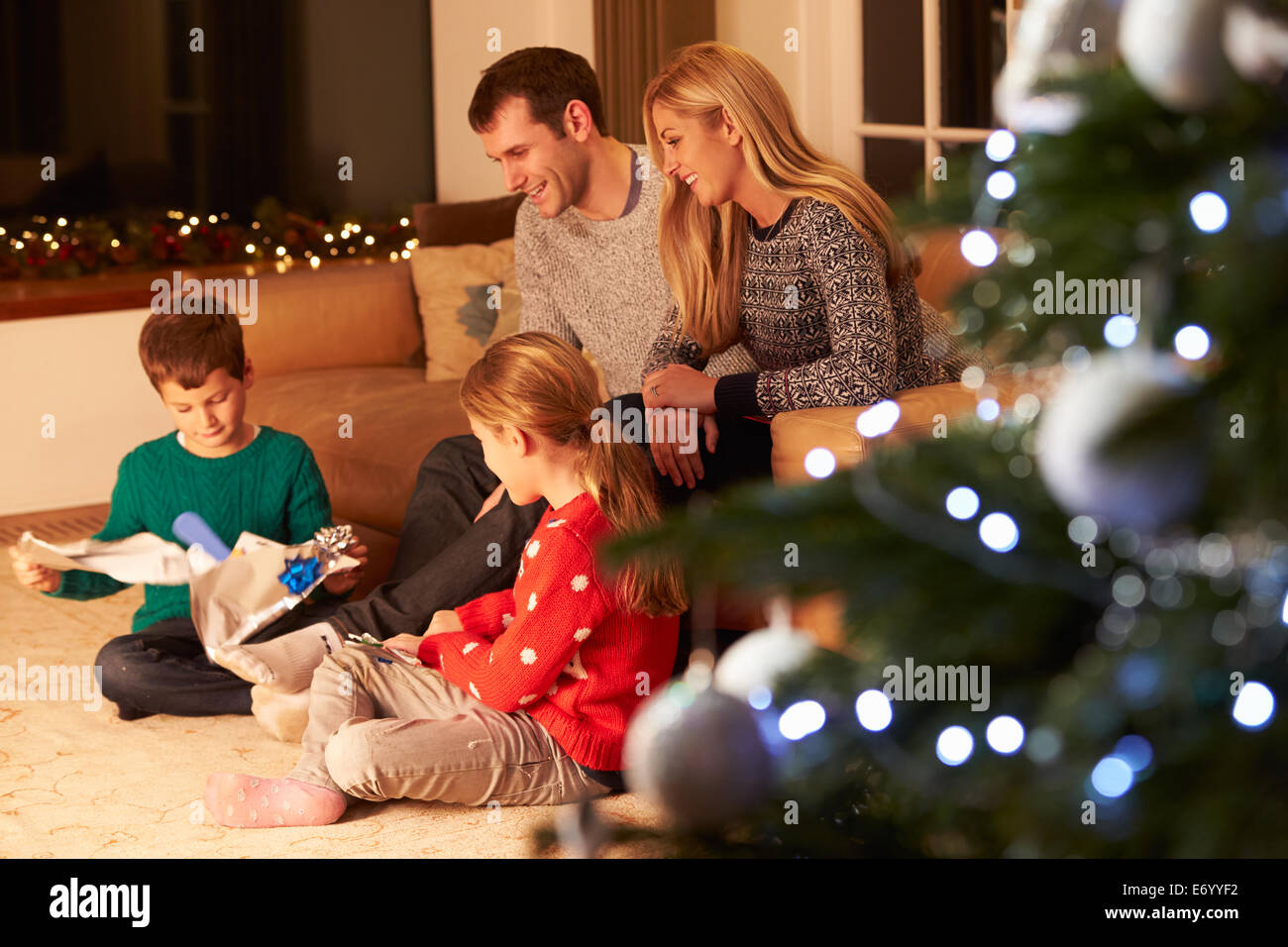 Family Unwrapping Gifts By Christmas Tree - Stock Image