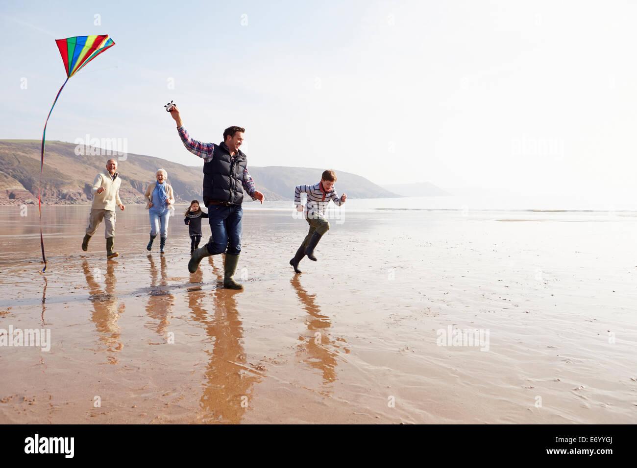 Multi Generation Family Flying Kite On Winter Beach - Stock Image