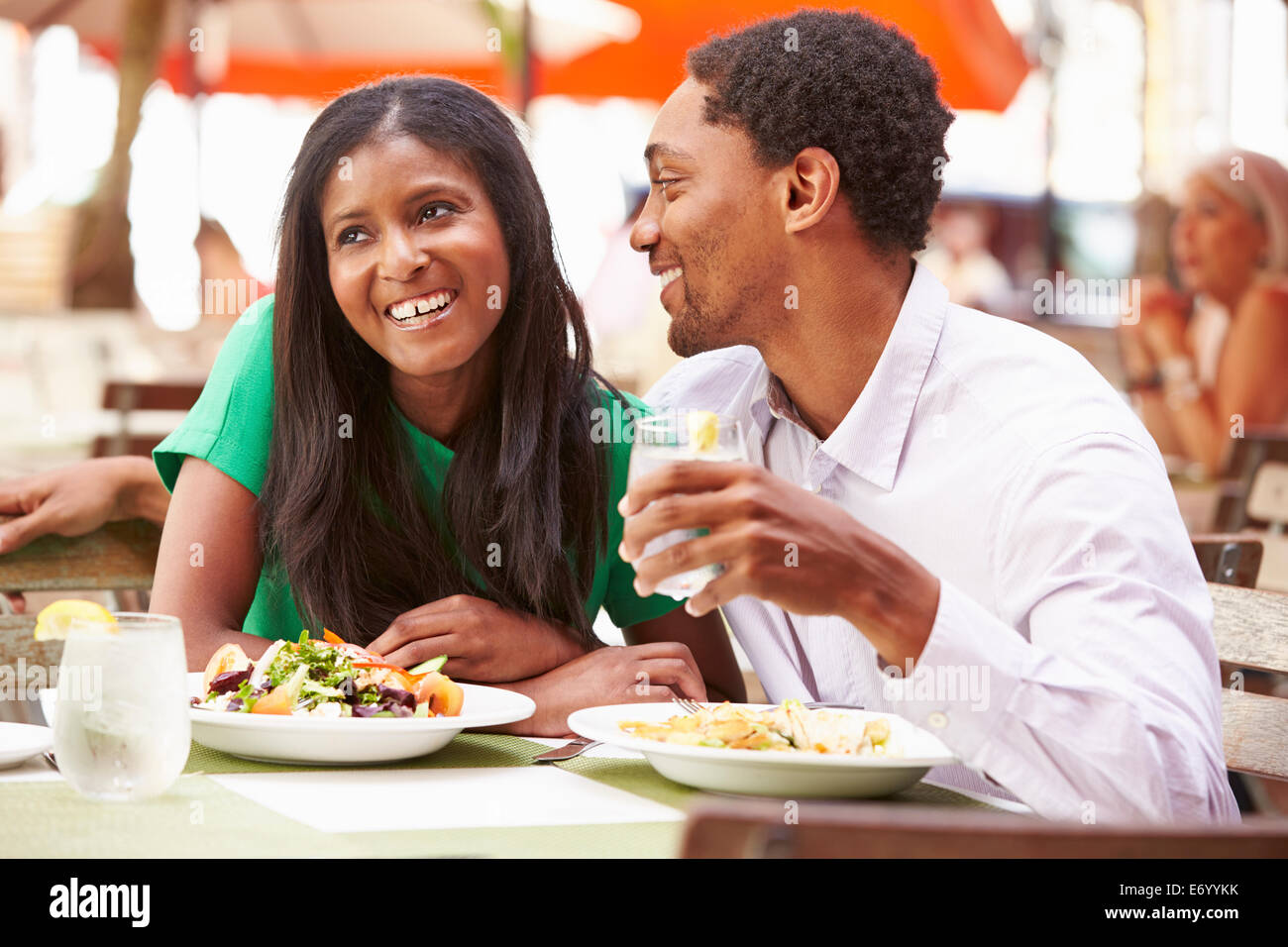 Couple Enjoying Lunch In Outdoor Restaurant - Stock Image