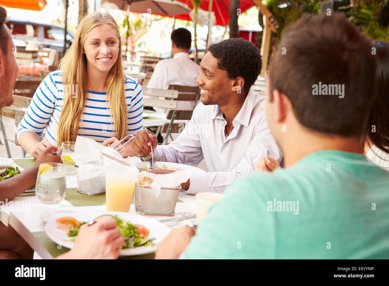 Group Of Friends Enjoying Lunch In Outdoor Restaurant - Stock Image