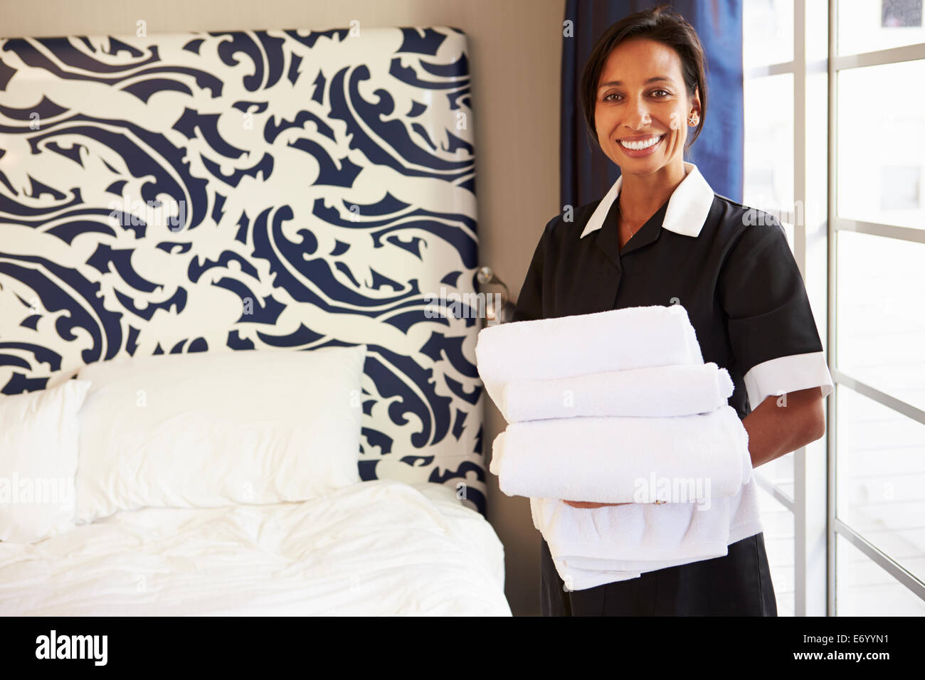 Portrait Of Maid Tidying Hotel Room - Stock Image