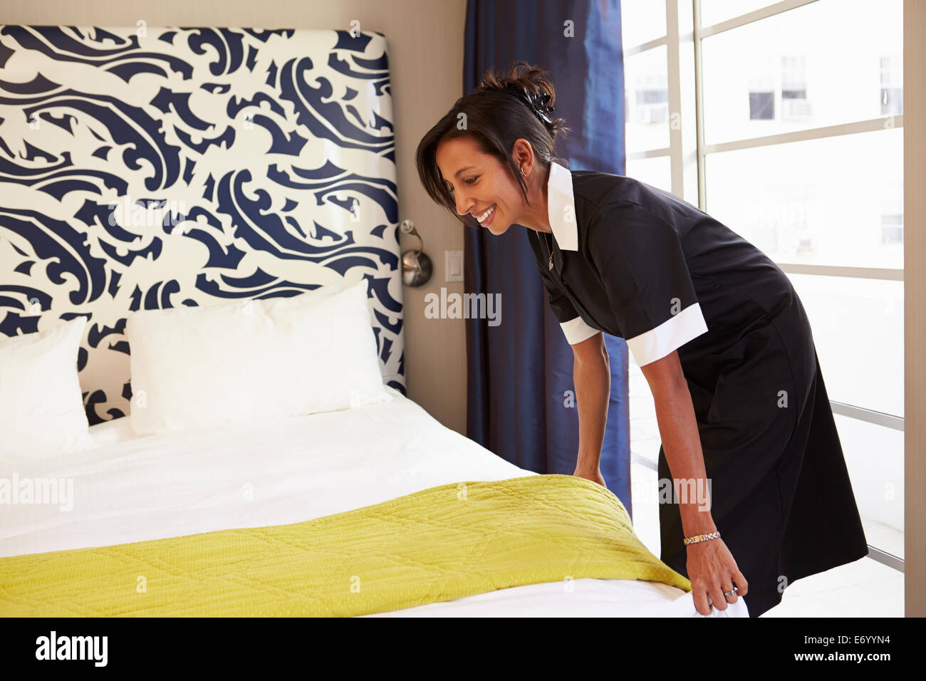 Maid Tidying Hotel Room And Making Bed - Stock Image