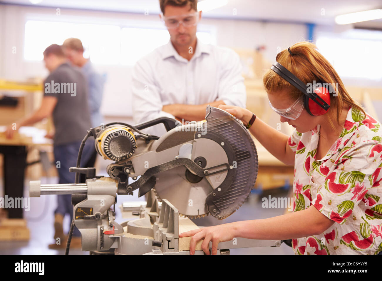 Student And Teacher In Carpentry Class Using Circular Saw - Stock Image