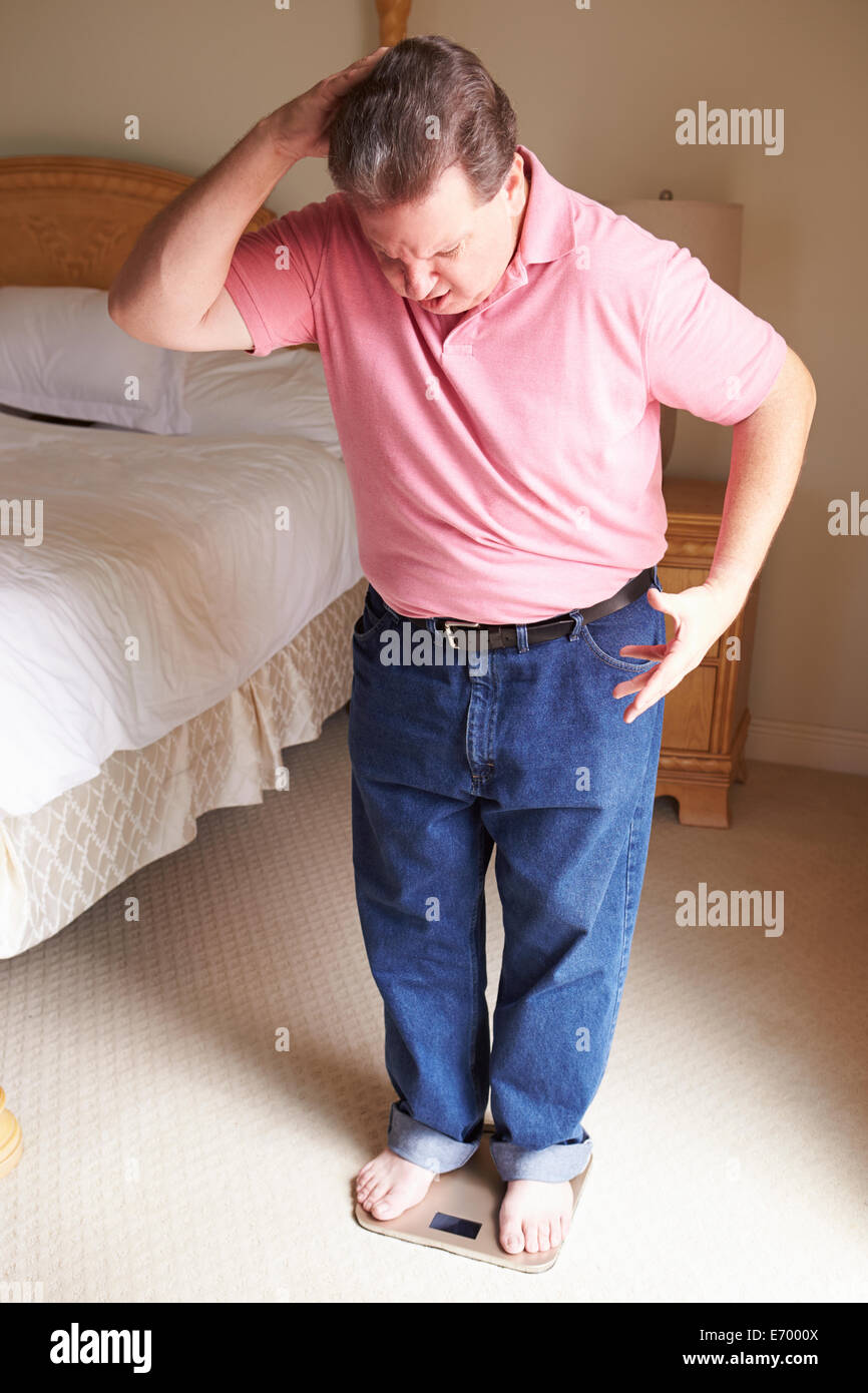 Overweight Man Weighing Himself On Scales In Bedroom - Stock Image