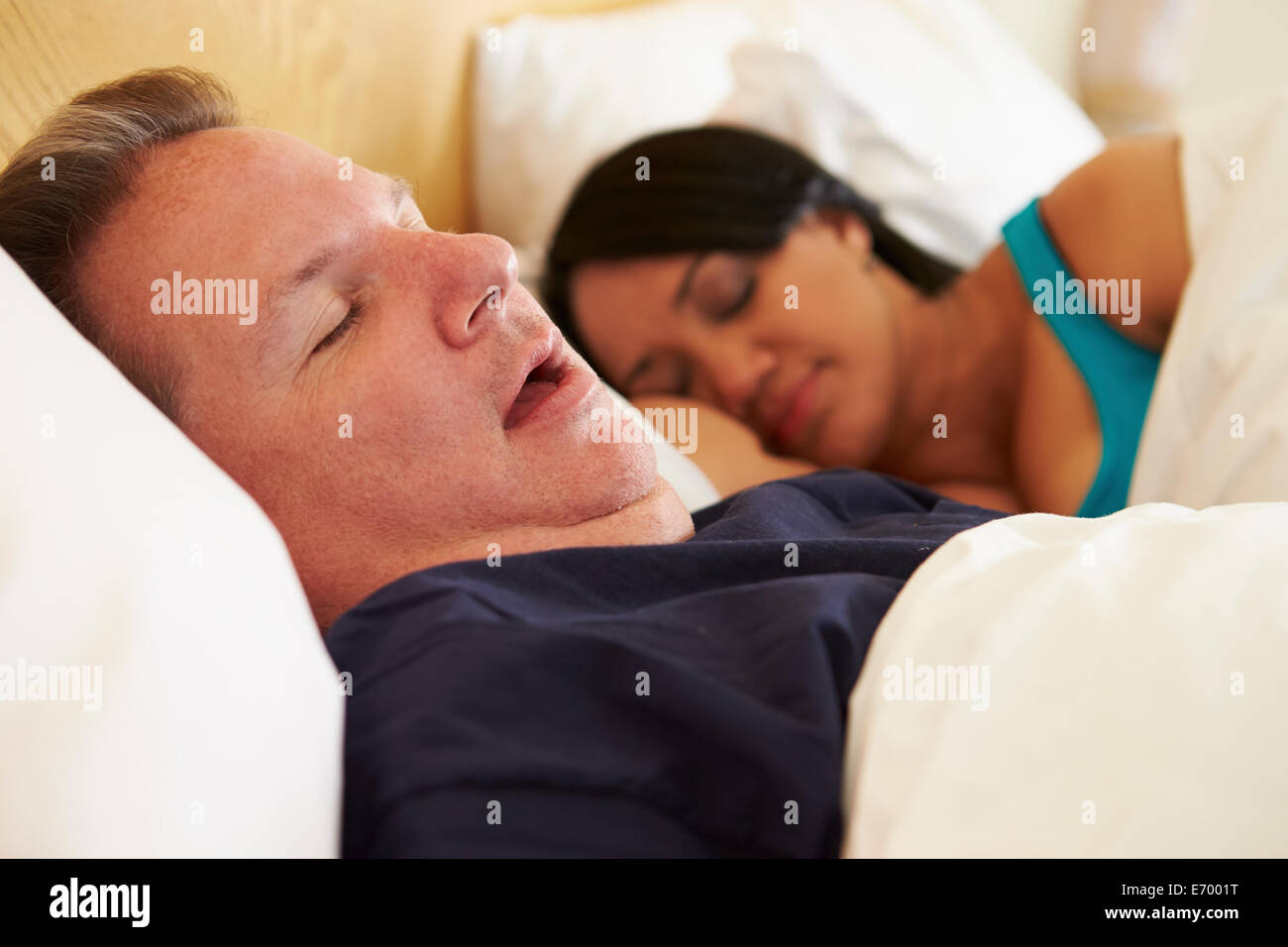 Couple Asleep In Bed With Man Snoring - Stock Image