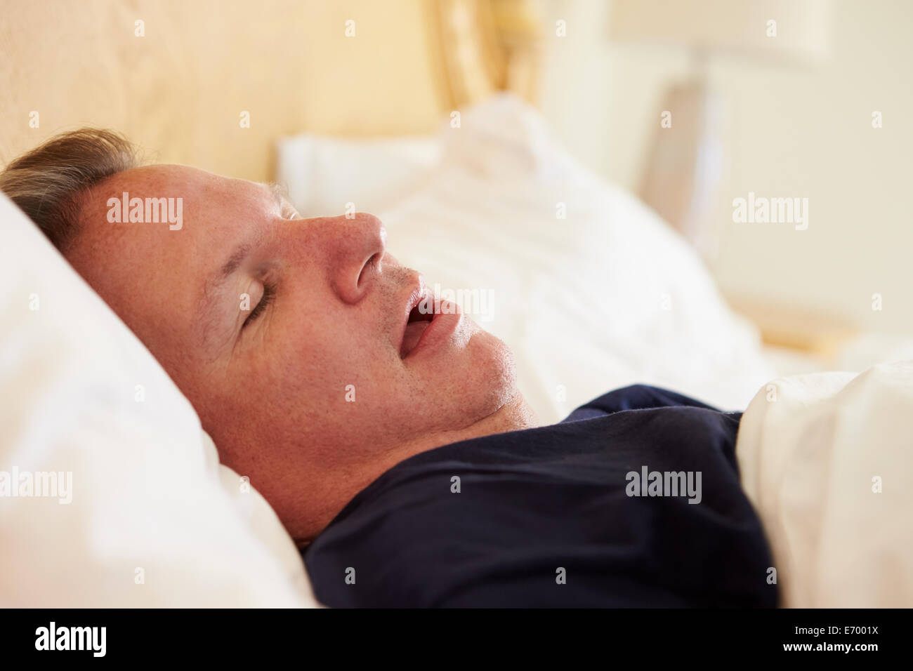 Overweight Man Asleep In Bed Snoring - Stock Image