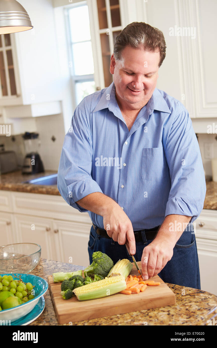 Overweight Man Preparing Vegetables in Kitchen - Stock Image
