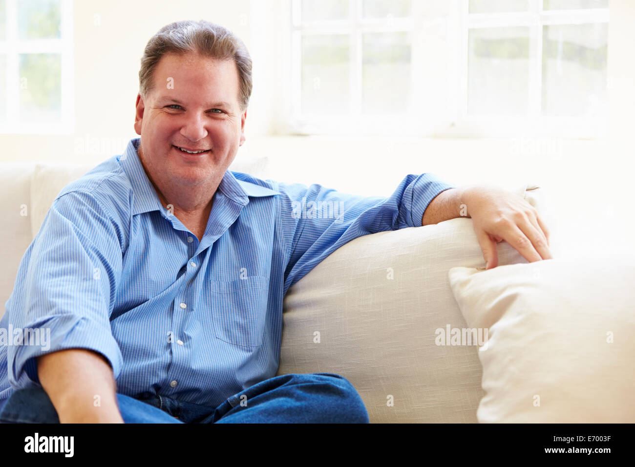 Portrait Of Overweight Man Sitting On Sofa - Stock Image