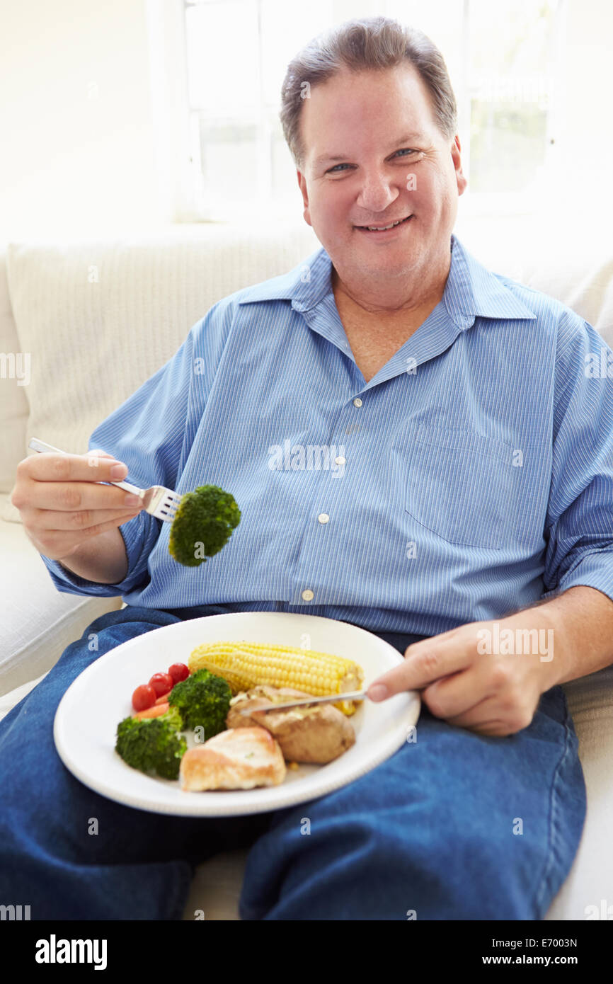 Overweight Man Eating Healthy Meal Sitting On Sofa - Stock Image