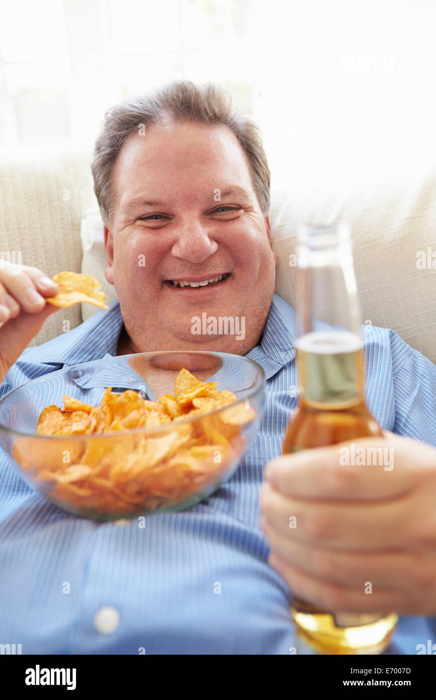 Overweight Man At Home Eating Chips And Drinking Beer Stock Photo