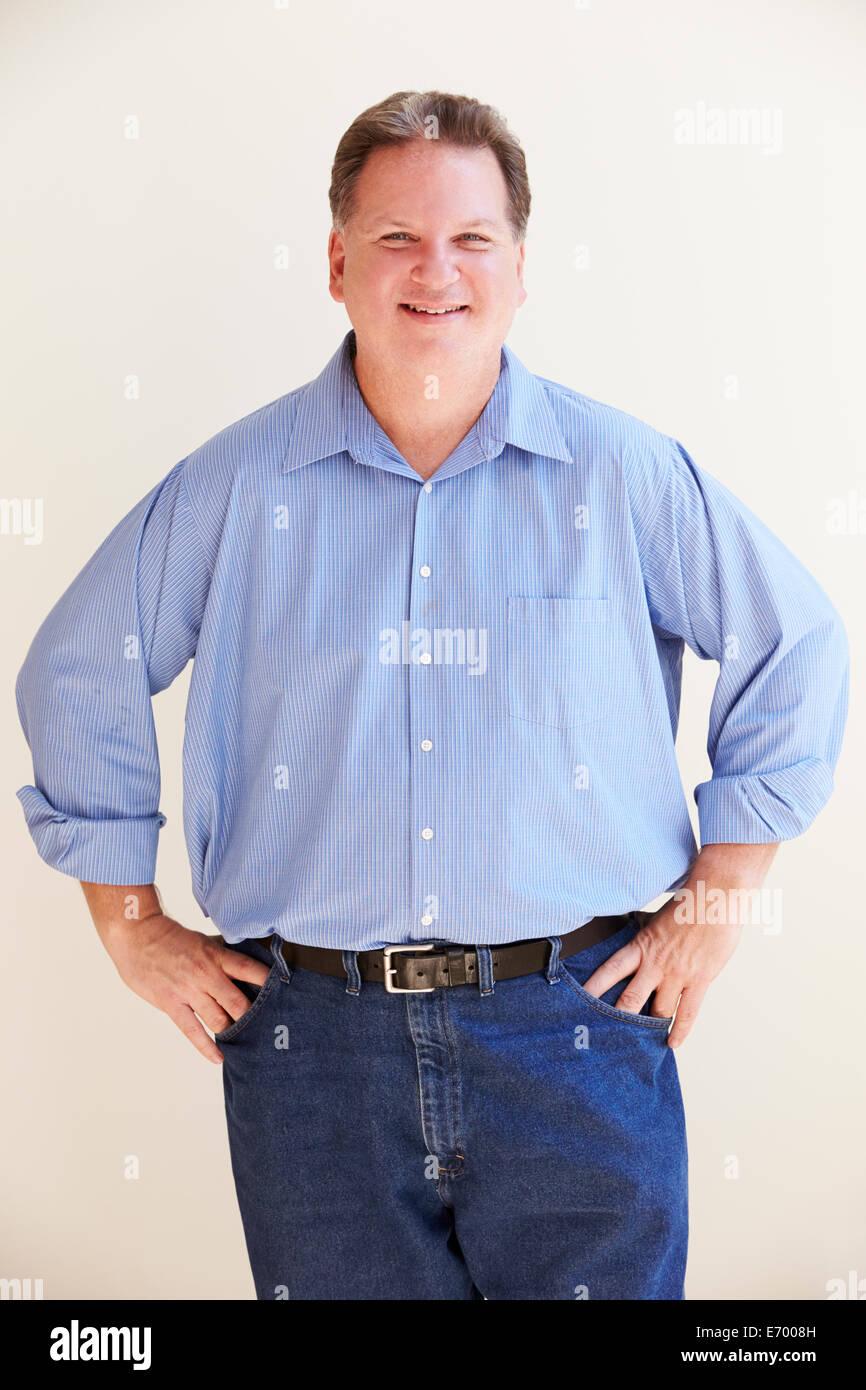Studio Portrait Of Smiling Overweight Man - Stock Image
