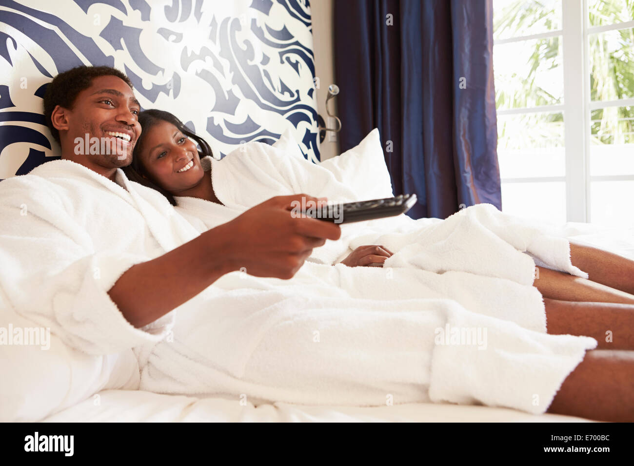 Couple Relaxing In Hotel Room Watching Television - Stock Image