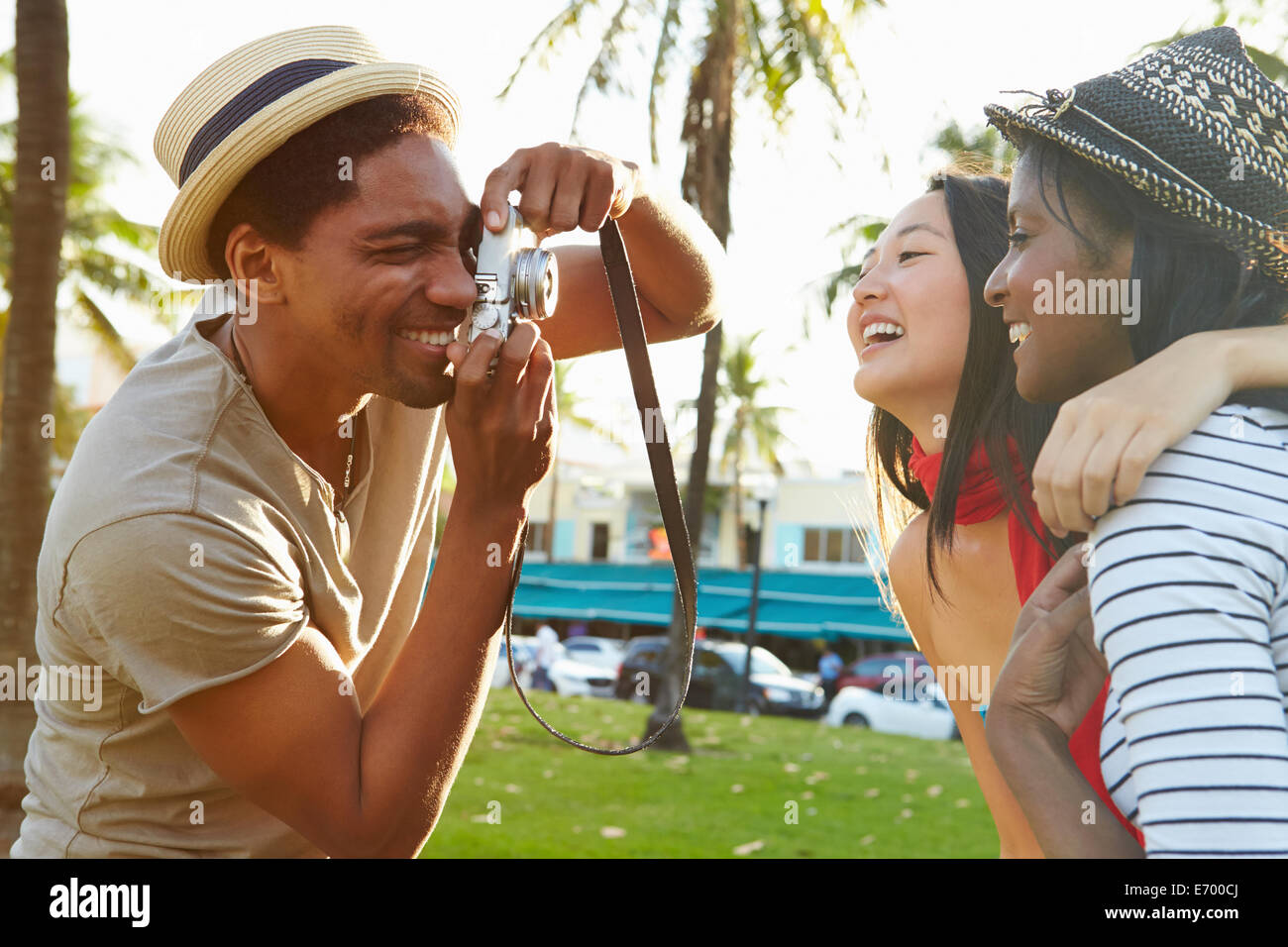 Man Taking Photograph Of Women In Park - Stock Image