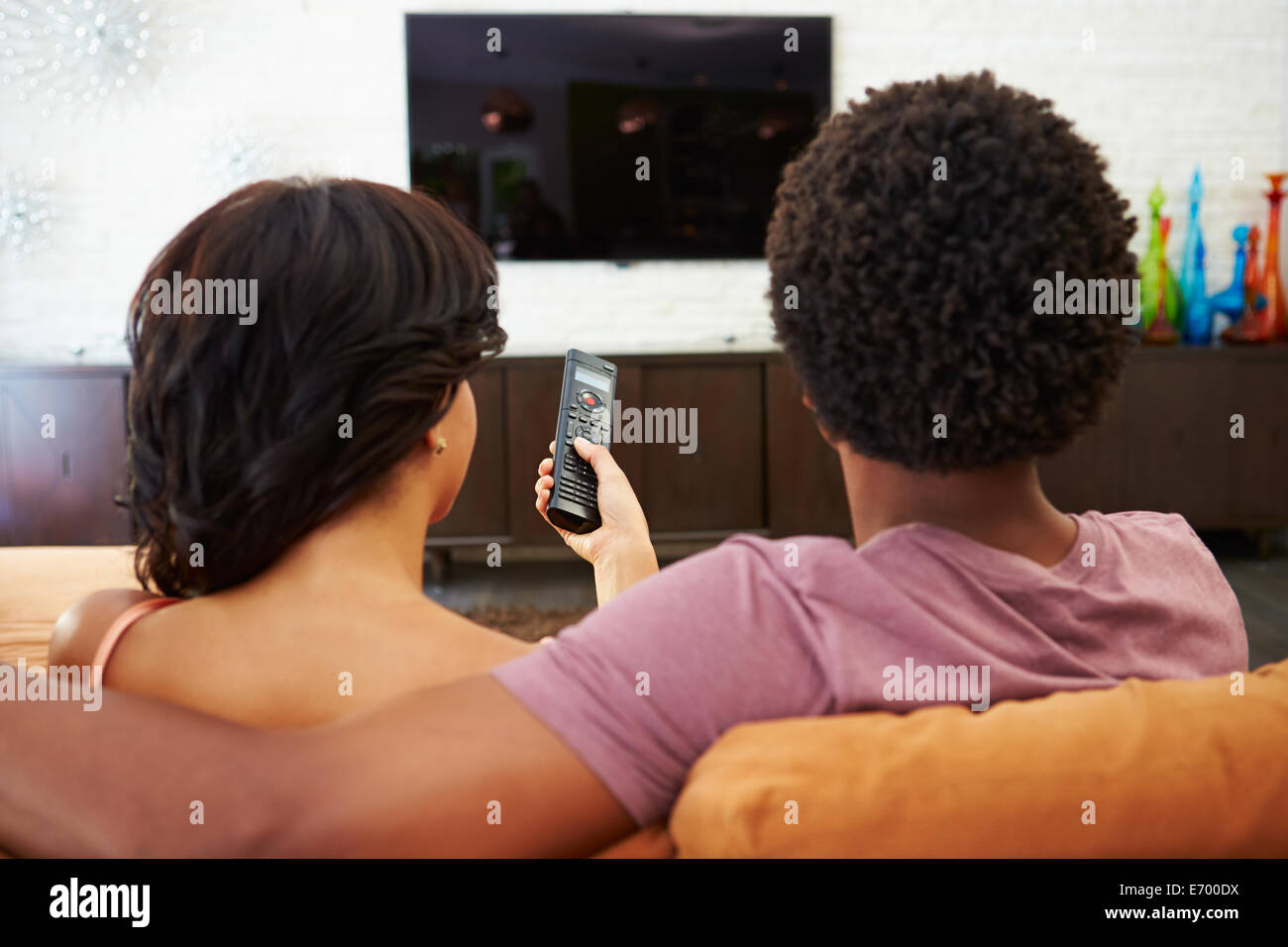 Rear View Of Couple Sitting On Sofa Watching TV Together - Stock Image