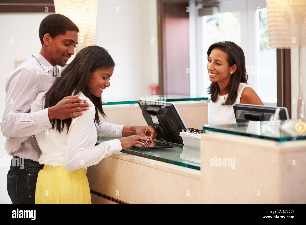 Couple Checking In At Hotel Reception Using Digital Tablet - Stock Image