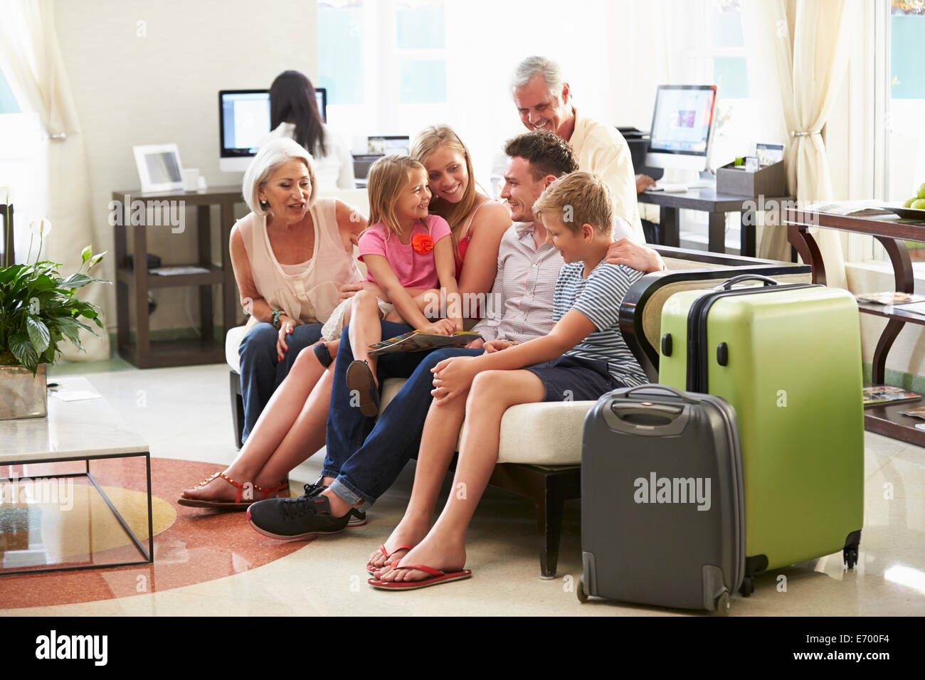 Multi Generation Family Arriving In Hotel Lobby - Stock Image
