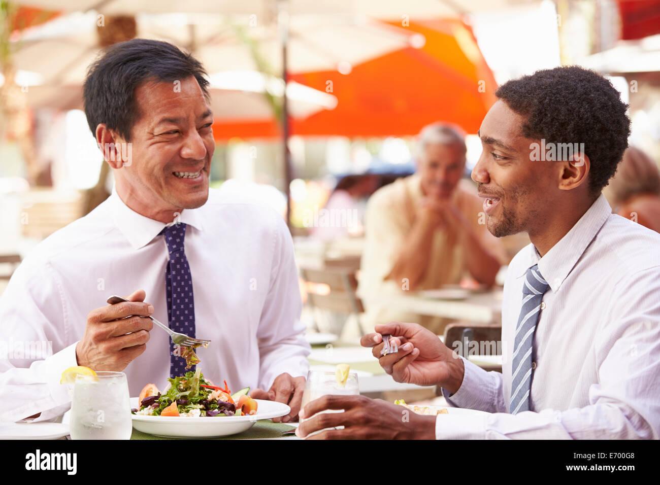 Two Businessmen Having Meeting In Outdoor Restaurant - Stock Image