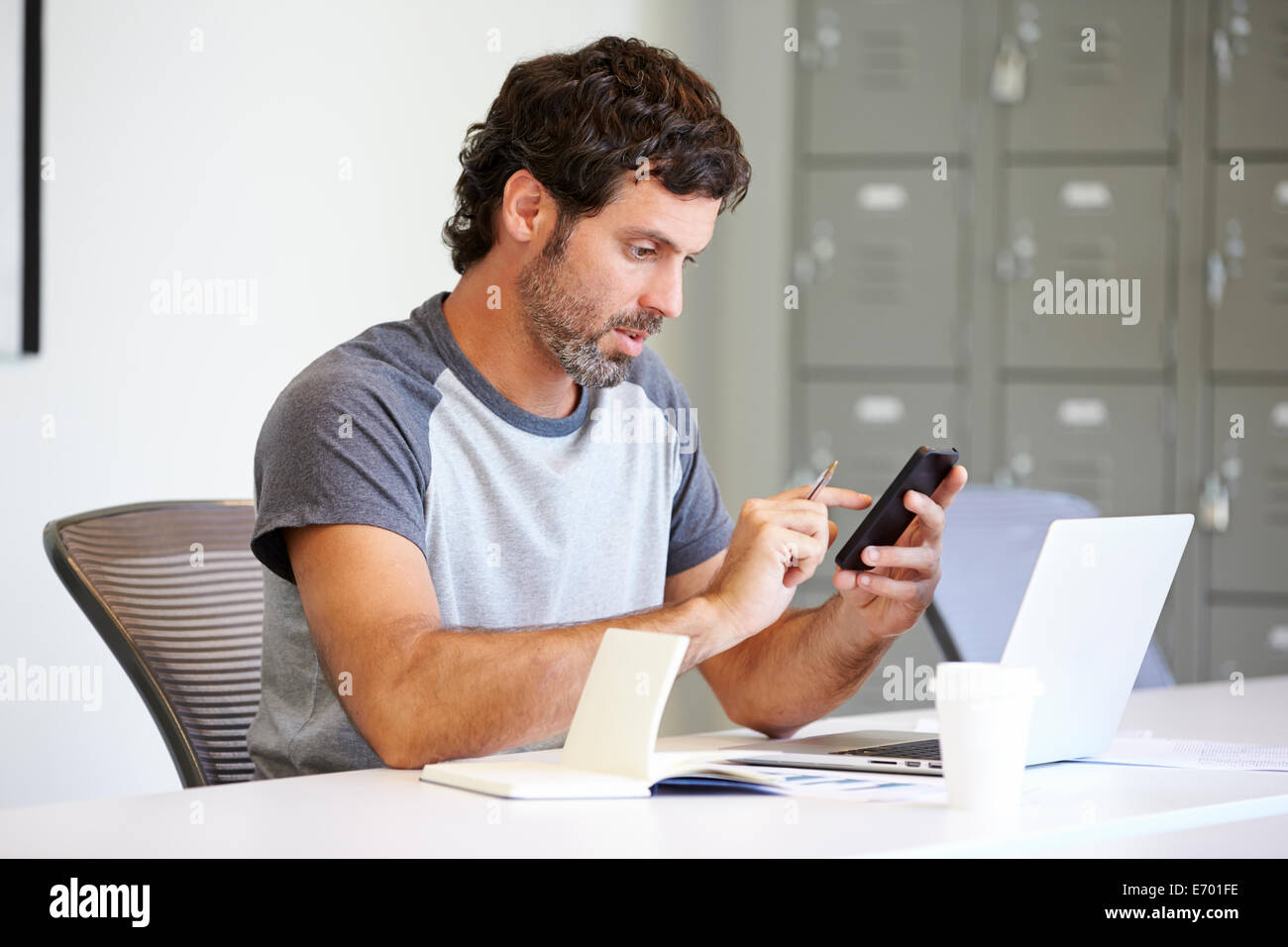 Casually Dressed Man Using Mobile Phone In Design Studio Stock Photo