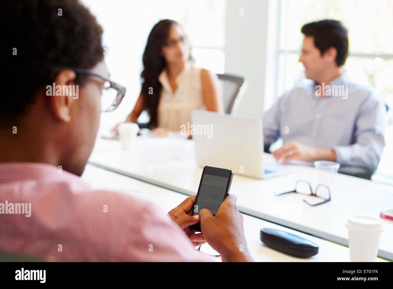 Designer Using Mobile Phone During Meeting - Stock Image
