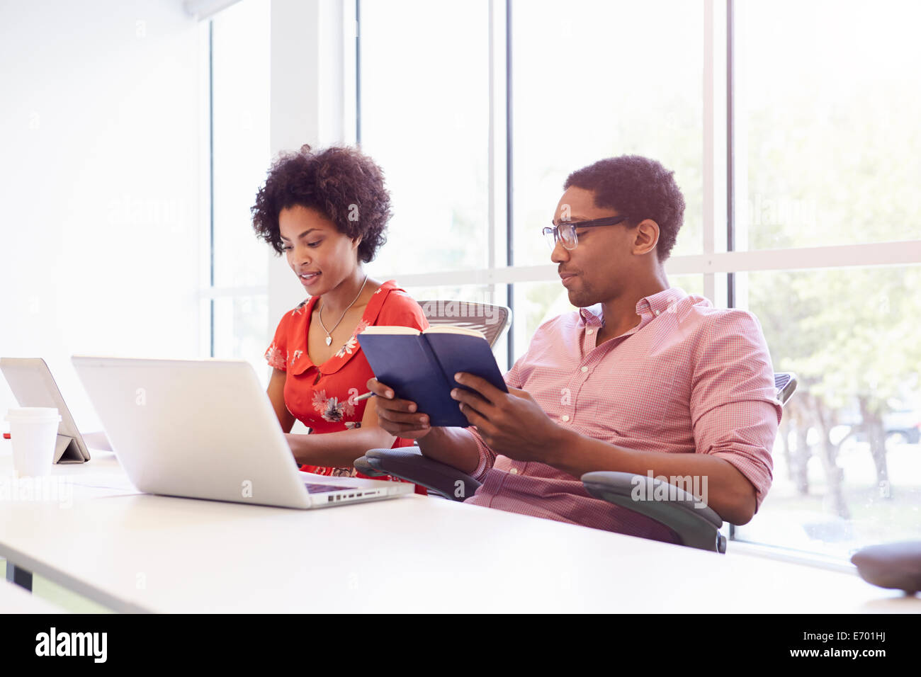 Two Creatives With Digital Tablet Working In Design Studio - Stock Image
