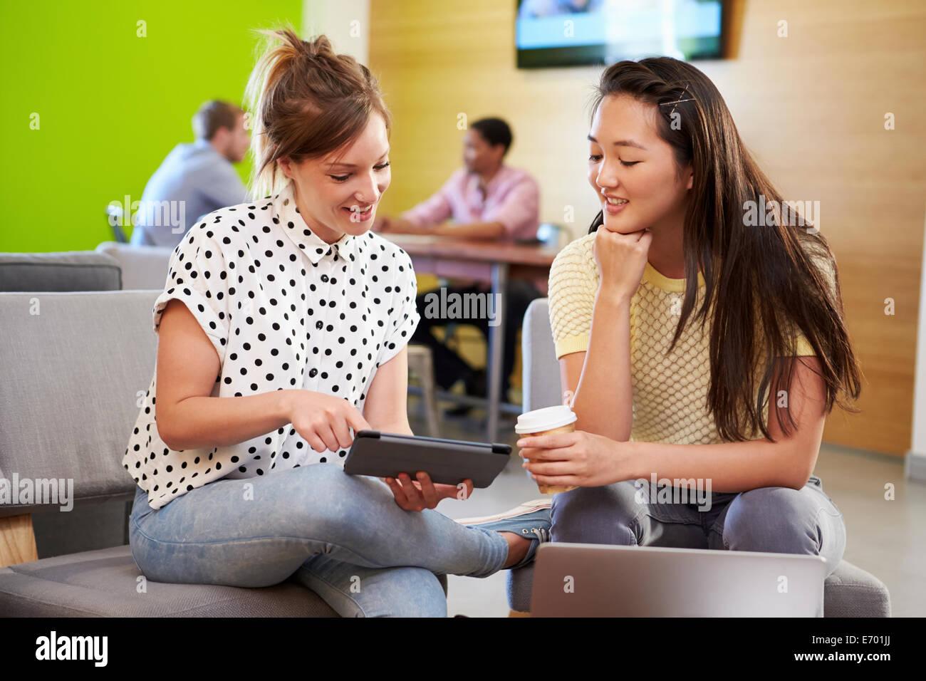Creatives Having Informal Meeting On Sofas In Design Studio - Stock Image