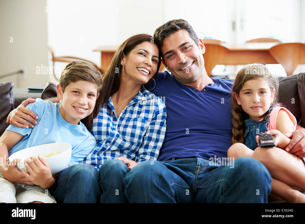 Family Sitting On Sofa Watching TV Together   Stock Image