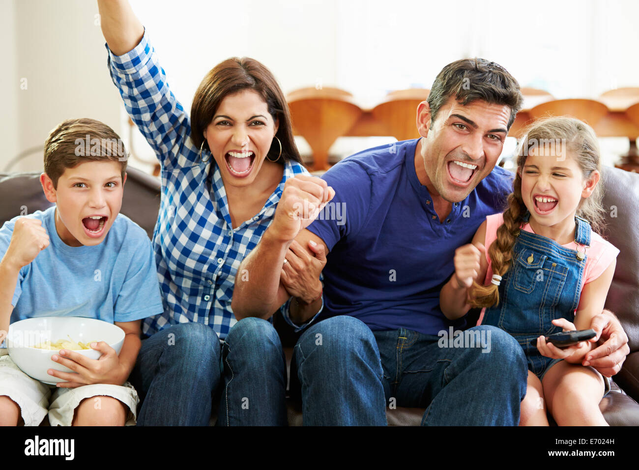 Family Watching Soccer Celebrating Goal - Stock Image