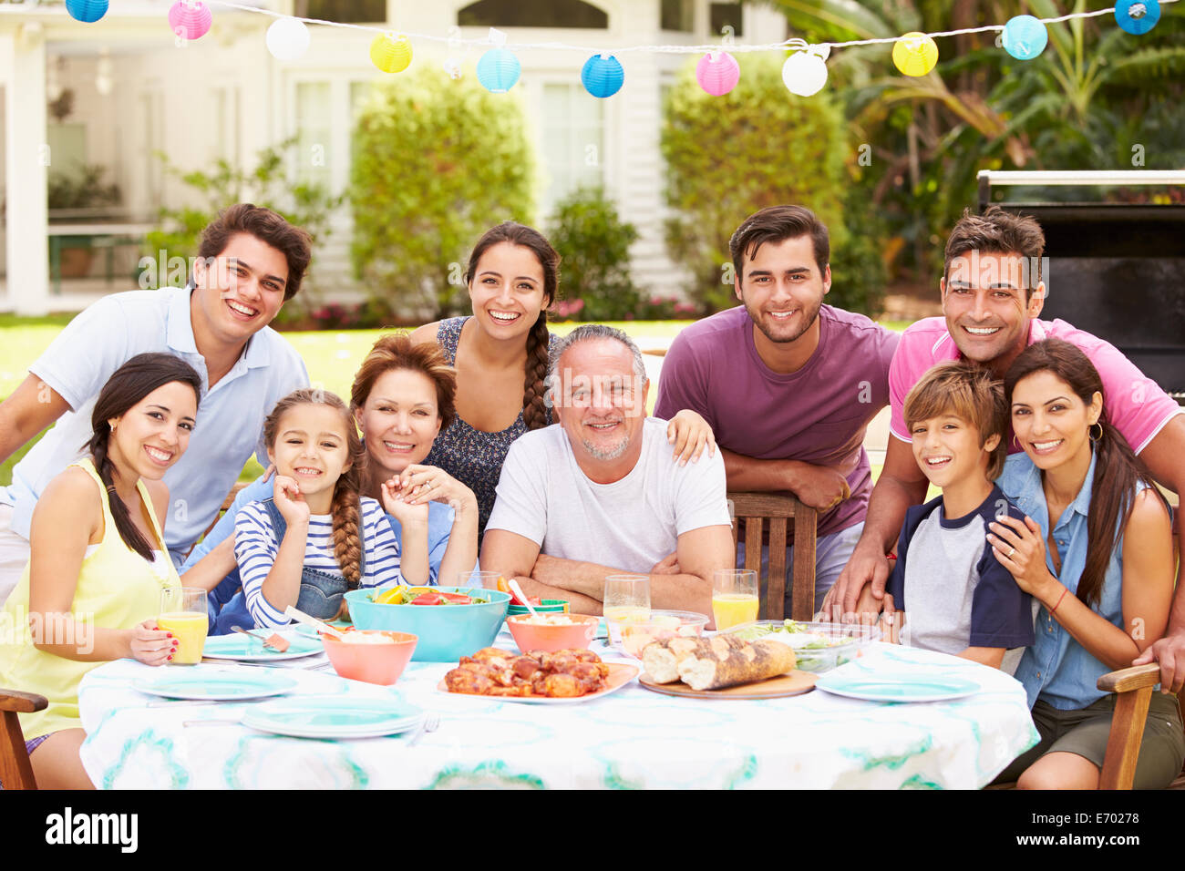 Multi Generation Family Enjoying Meal In Garden Together - Stock Image