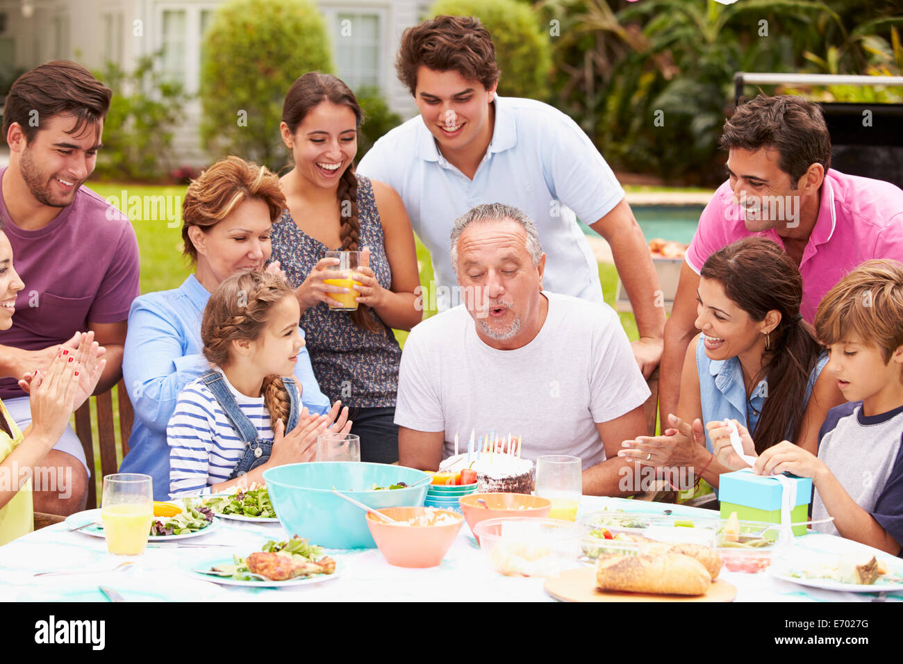Multi Generation Family Celebrating Birthday In Garden - Stock Image