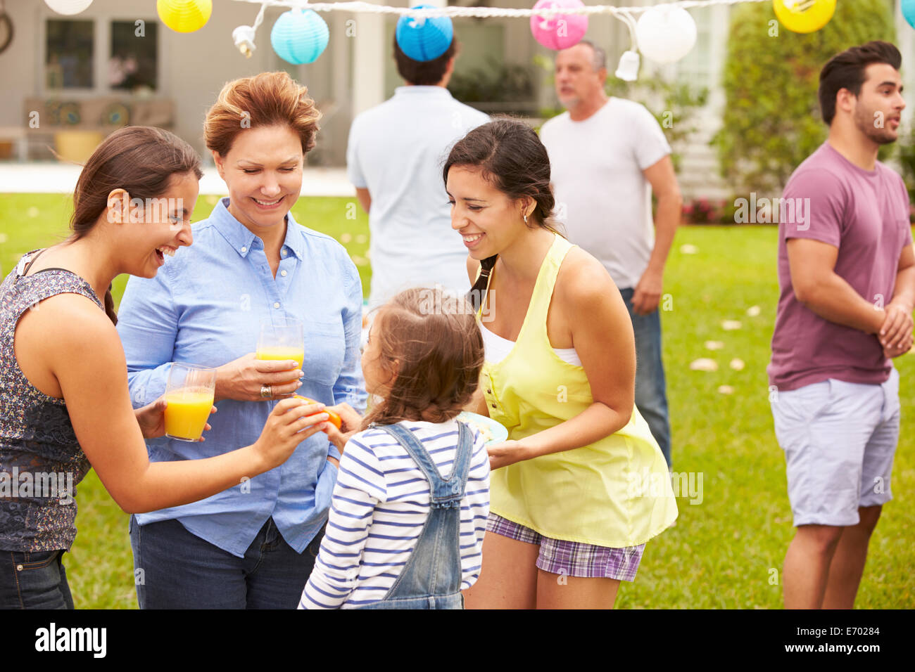 Multi Generation Family Enjoying Party In Garden Together - Stock Image