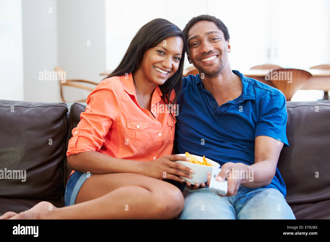 Couple Sitting On Sofa Watching TV Together - Stock Image