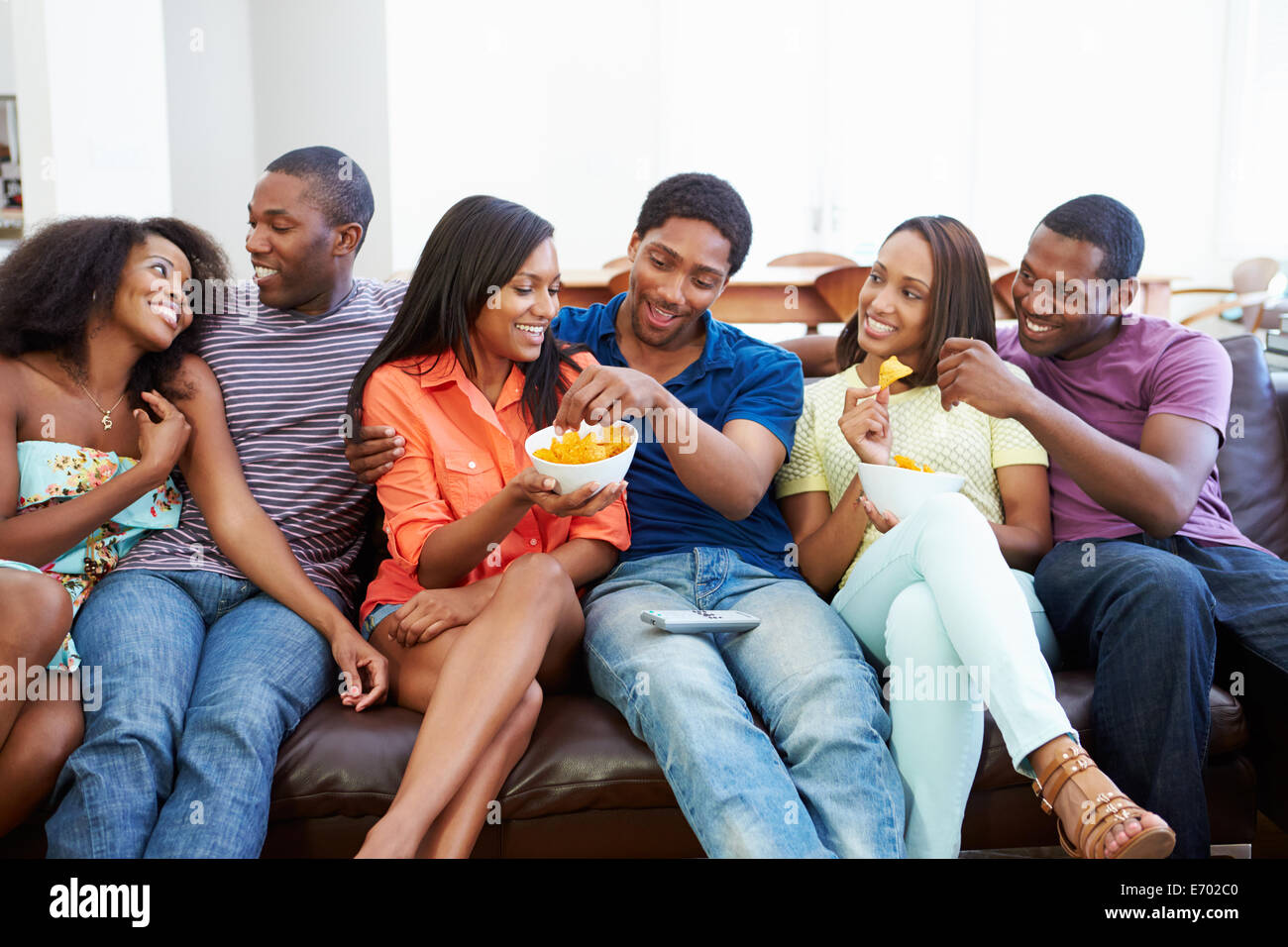 Group Of Friends Sitting On Sofa Watching TV Together - Stock Image