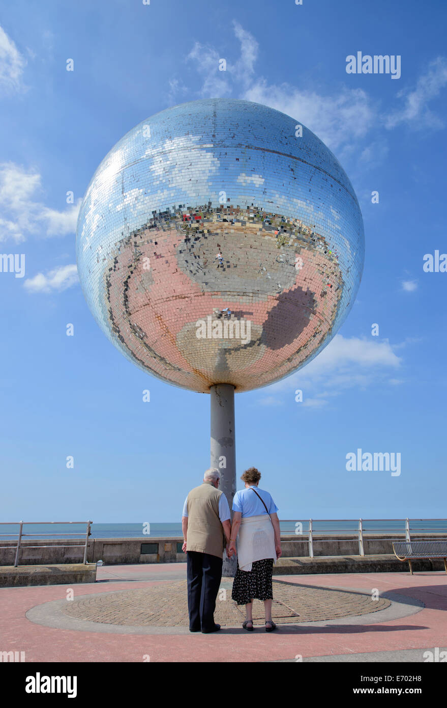 Two people looking at the rotating giant mirror ball on the South Shore promenade in Blackpool, Lancashire, UK - Stock Image