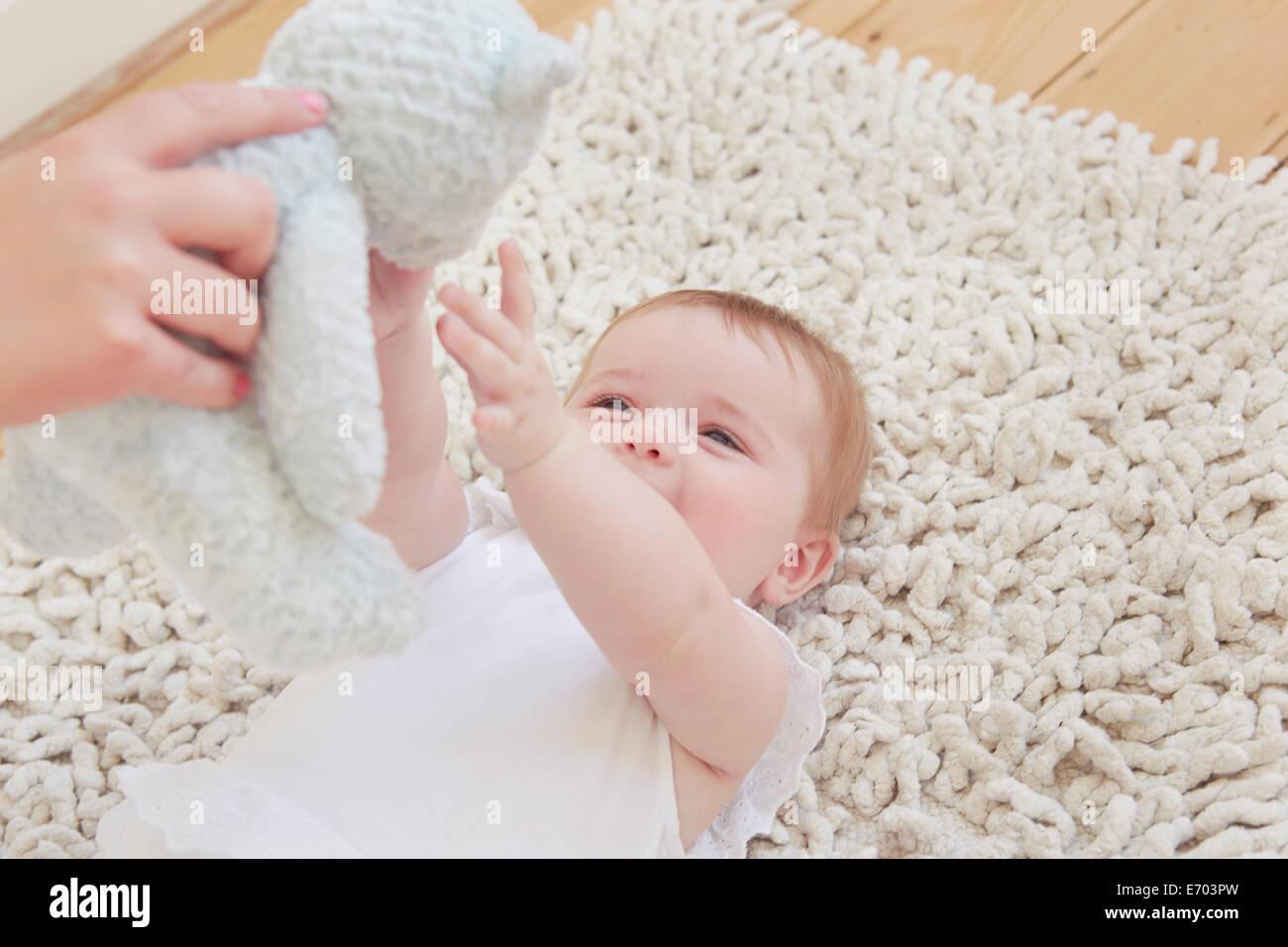 Female hand holding up teddy bear for baby girl lying on rug - Stock Image