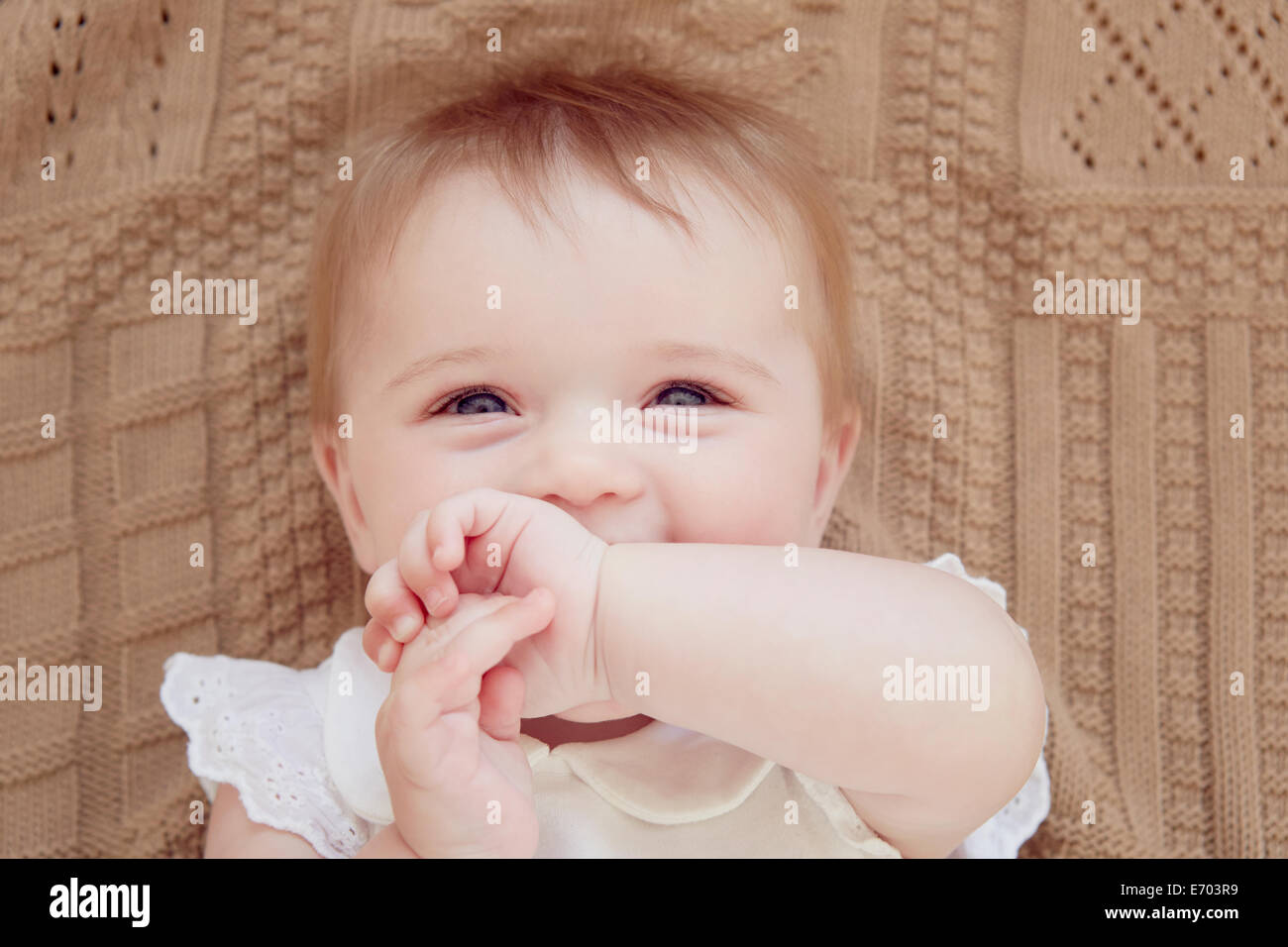 Close up portrait of smiling baby girl lying on blanket - Stock Image