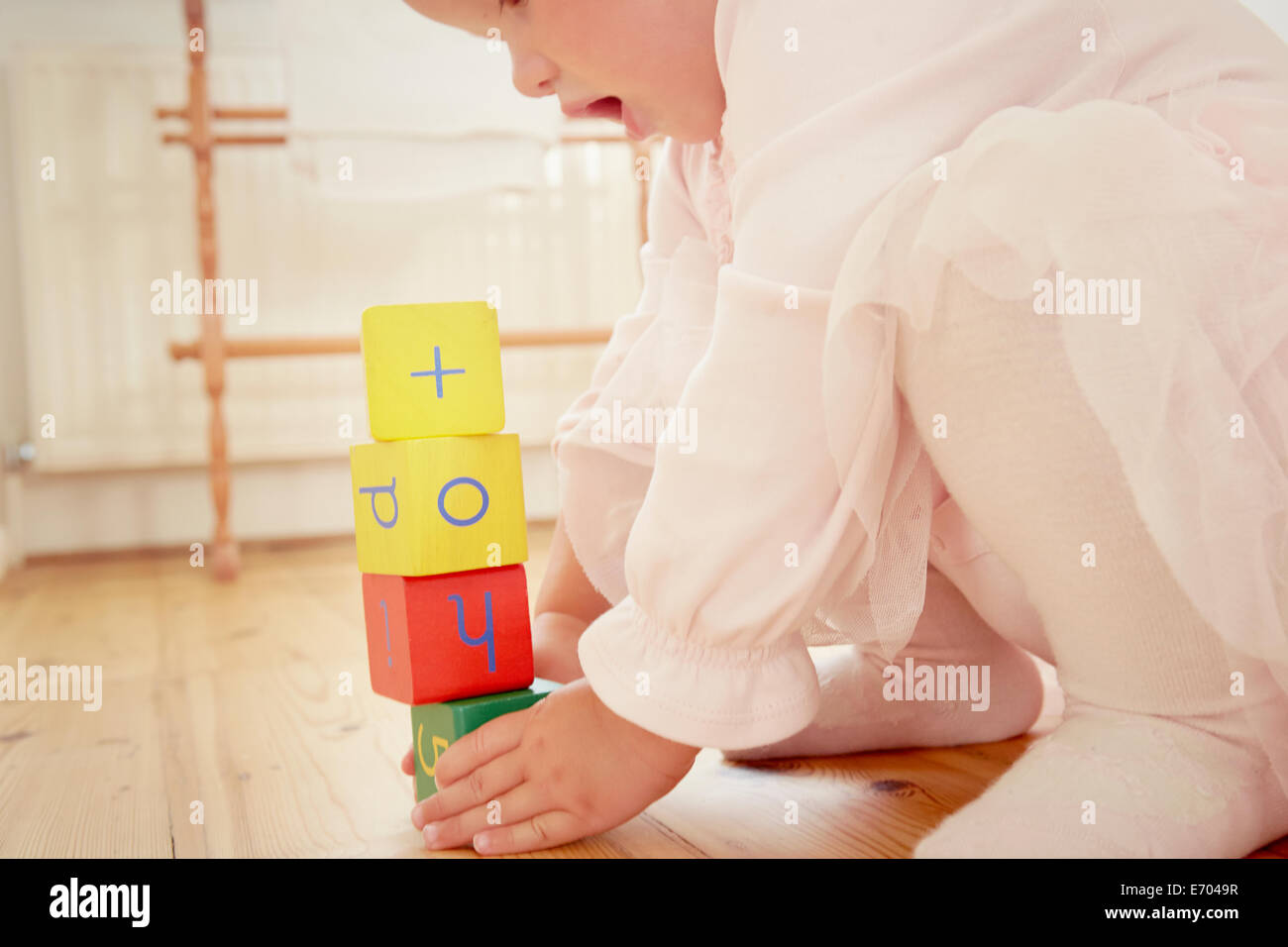 Cropped shot of baby girl building stack with building blocks - Stock Image