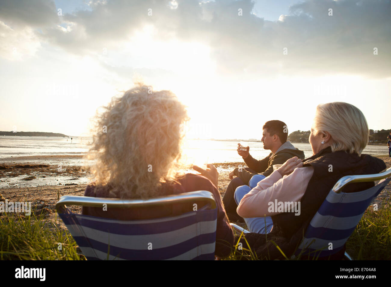 Family members relaxing by beach - Stock Image