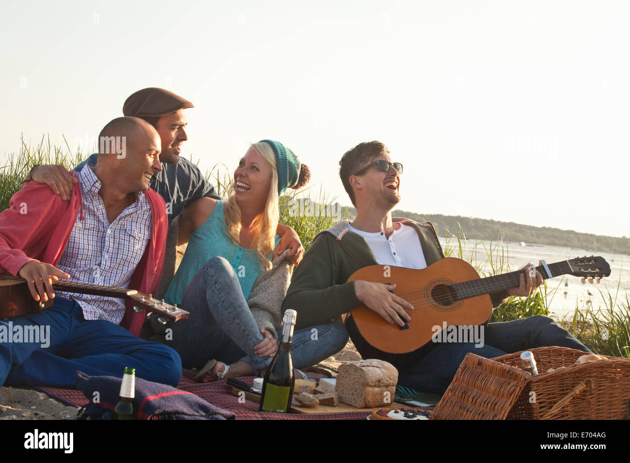 Four adult friends having a party on Bournemouth beach, Dorset, UK - Stock Image