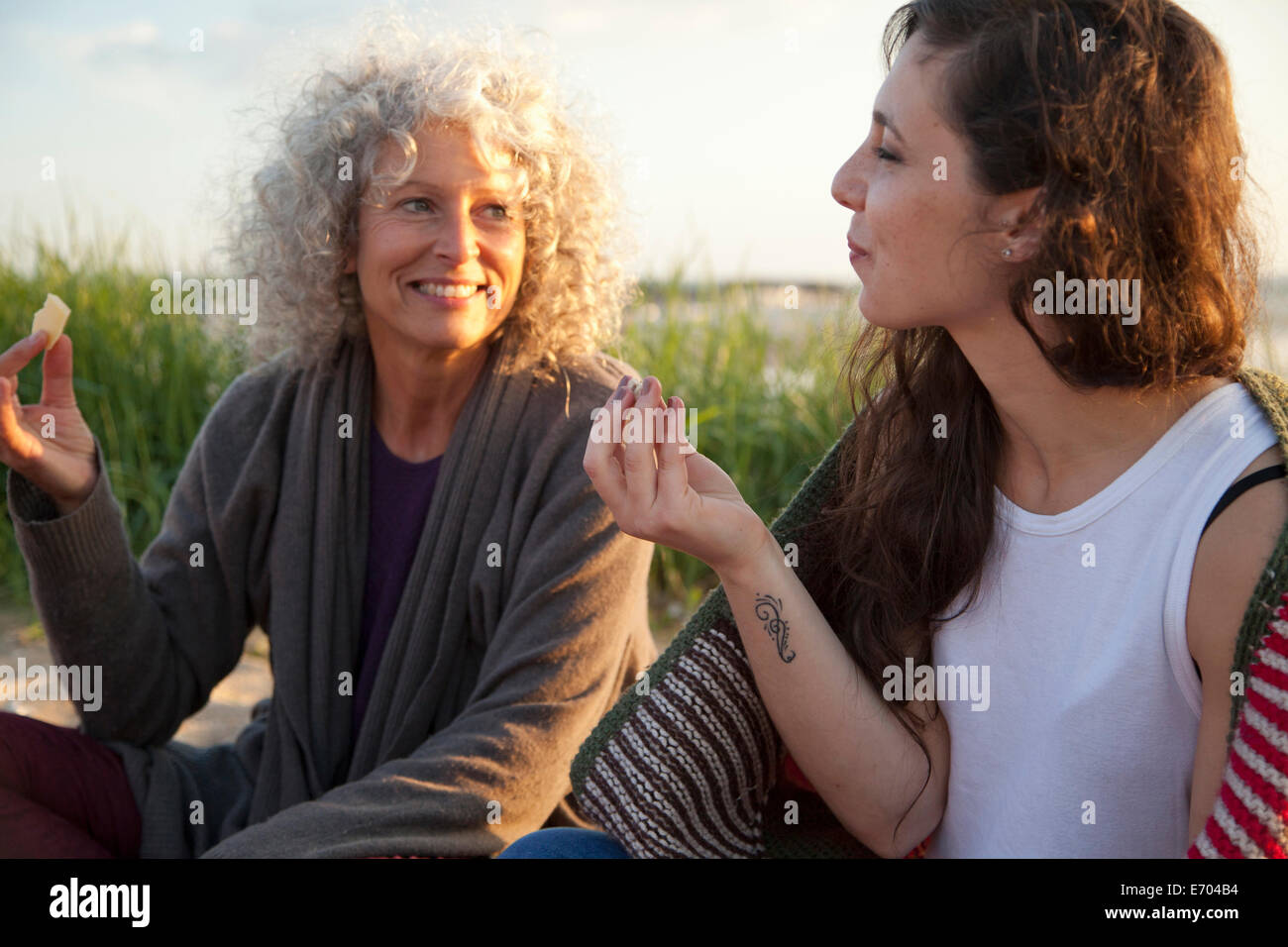 Two women having picnic on Bournemouth beach, Dorset, UK - Stock Image