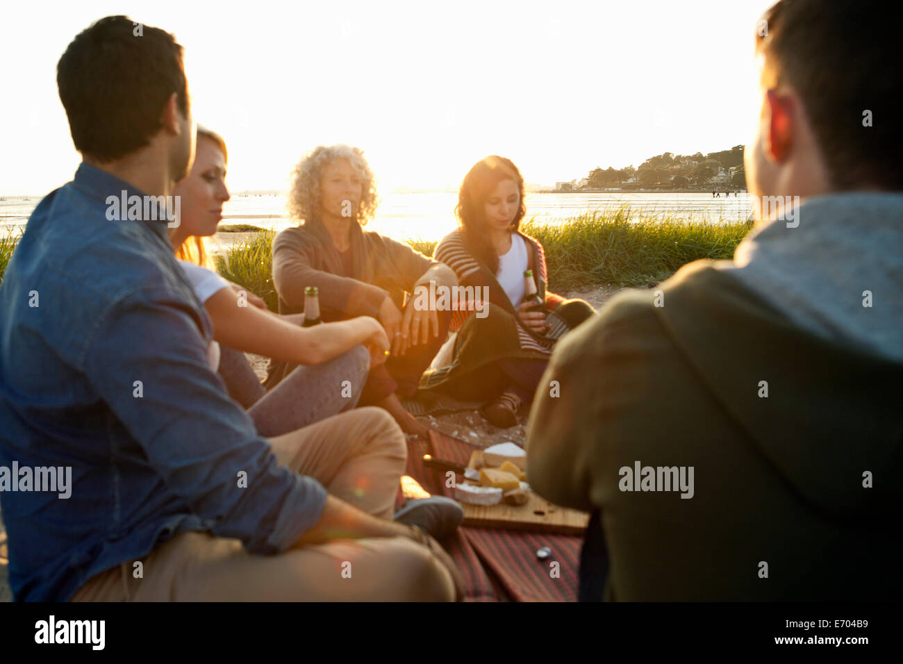 Five adult friends having picnic on Bournemouth beach, Dorset, UK - Stock Image