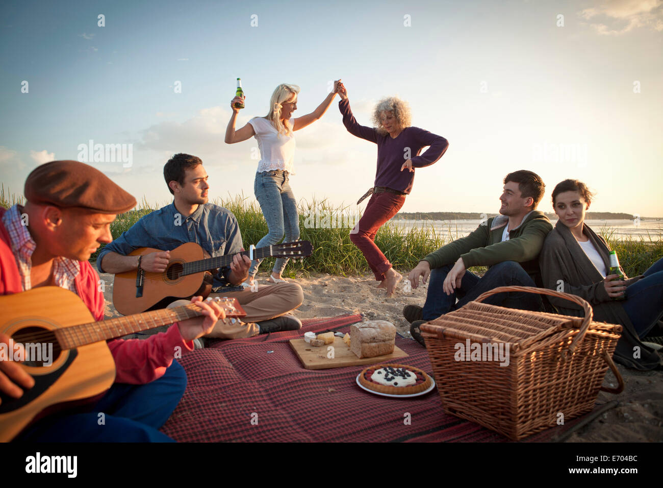 Six adult friends partying and dancing on Bournemouth beach, Dorset, UK - Stock Image