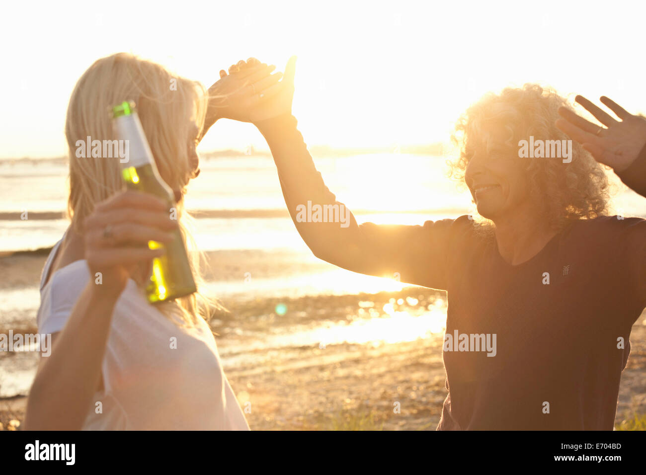 Mature mother and daughter dancing on Bournemouth beach, Dorset, UK Stock Photo